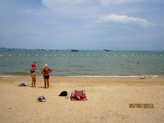 Tourists sunbathing along the shoreline of Pattaya beach