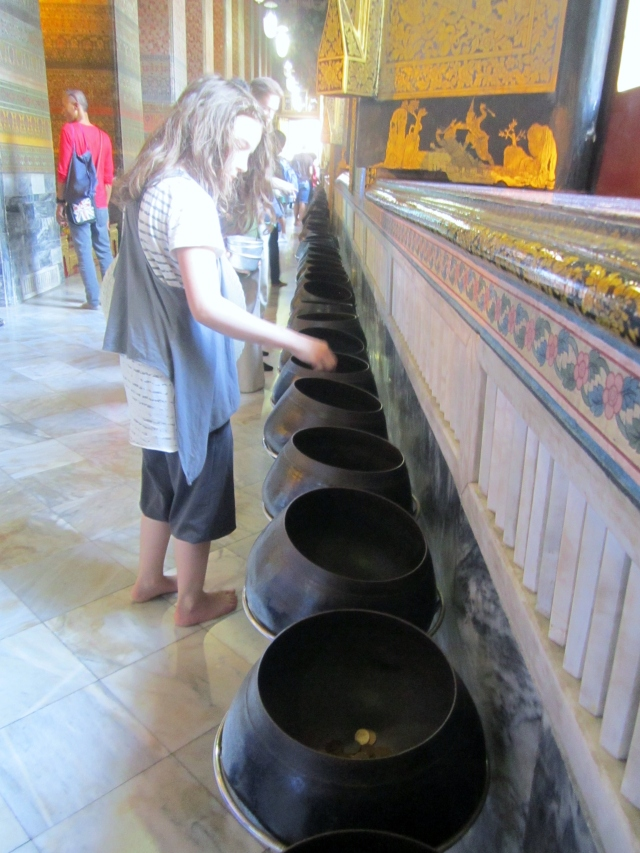 108 bronze bowls (said to  the 108 auspicious characters of Buddha) lined up where people drop coins